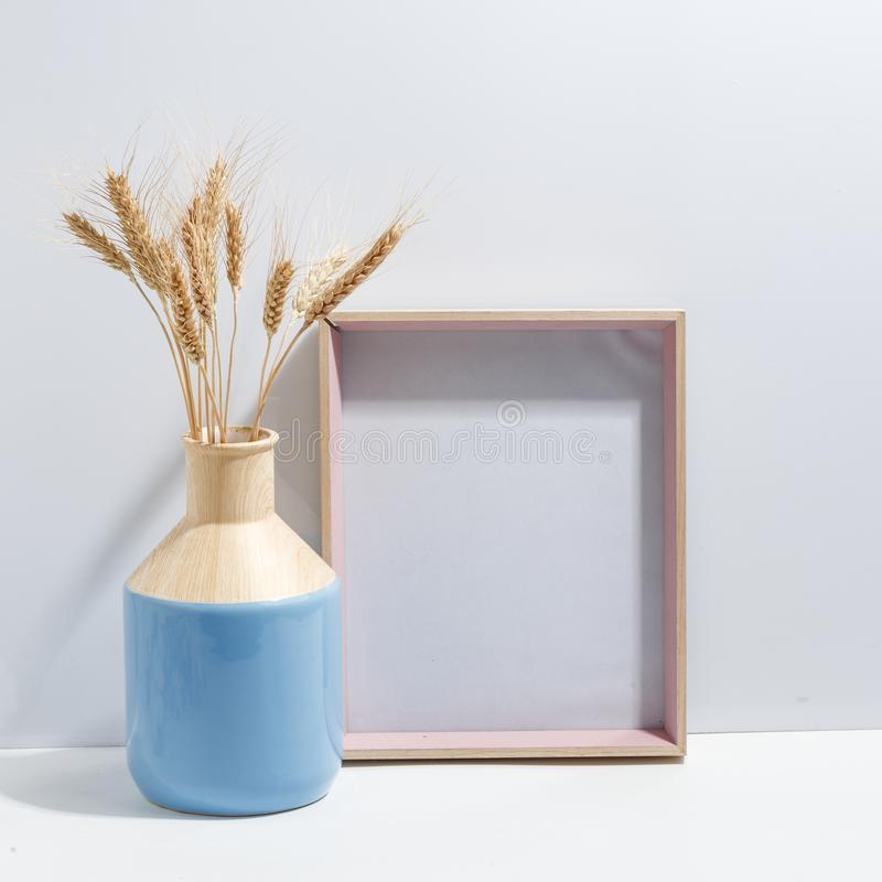 Åtlöje upp den vita ramen och spikelets av vete i blå vas på det bokhylla eller skrivbordet Minimalistic begrepp royaltyfria bilder