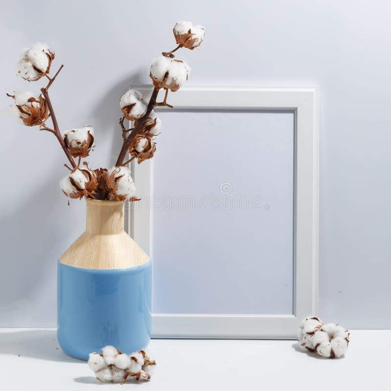 Åtlöje upp den vita ramen och torrt bomullsris i blå vas på det bokhylla eller skrivbordet Minimalistic begrepp arkivfoton