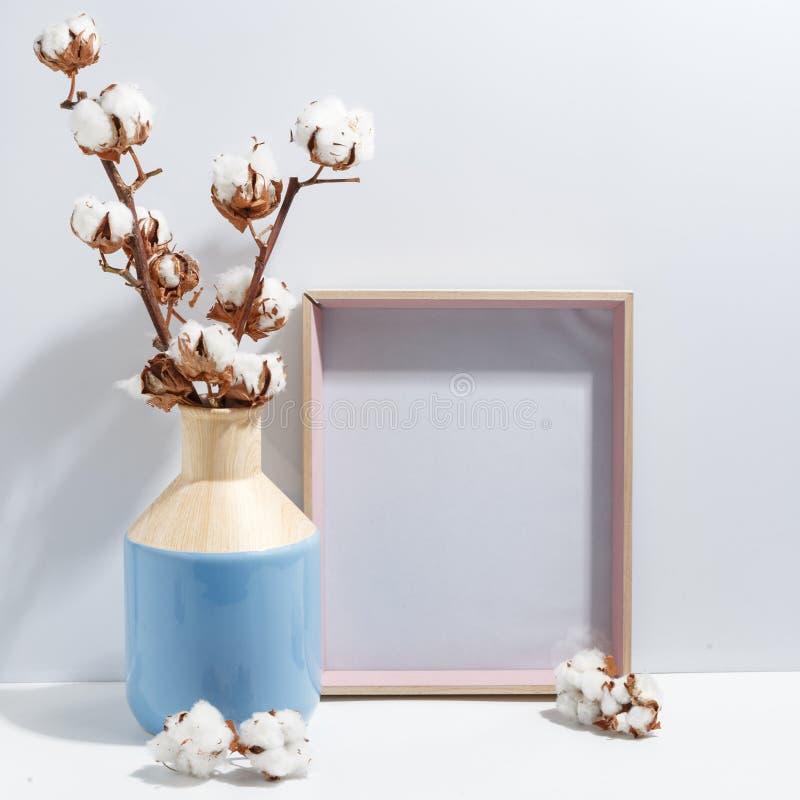 Åtlöje upp den vita ramen och torrt bomullsris i blå vas på det bokhylla eller skrivbordet Minimalistic begrepp royaltyfri fotografi