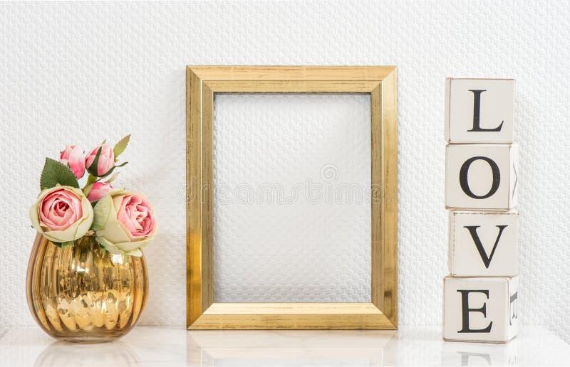 Åtlöje upp med den guld- ramen och blommor man för begreppskyssförälskelse till kvinnan arkivfoto