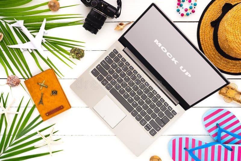 Åtlöje upp skärm av bärbara datorn på den vita trätabellen för begrepp för bakgrund för semester för sommarferie Plan lekmanna- b royaltyfria bilder