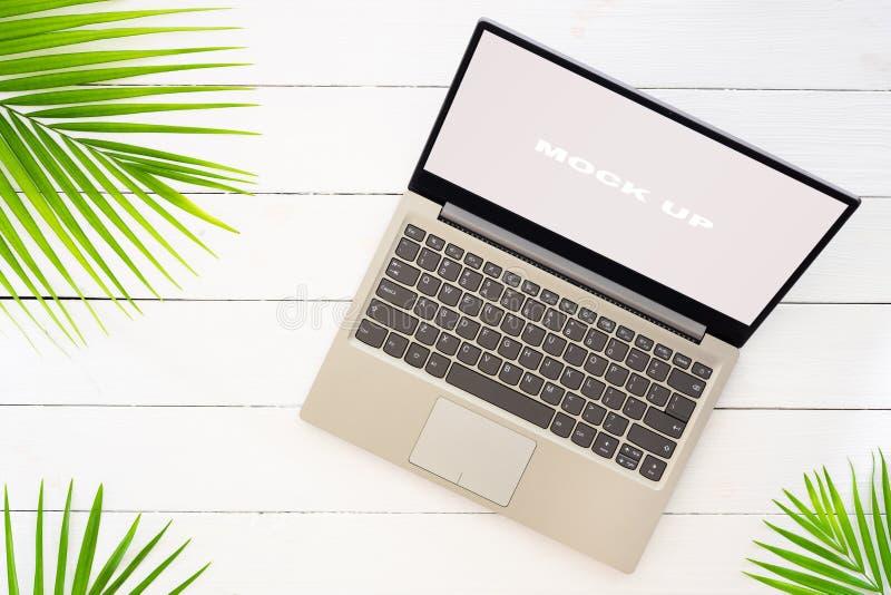 Åtlöje upp skärm av bärbara datorn på den vita trätabellen för begrepp för bakgrund för sommarferie Plan lekmanna- bästa sikt av  royaltyfri bild
