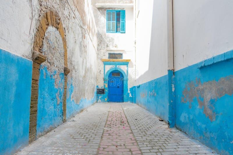 Åtsittande och smal blå och vit gata i Medinaen av Essaouira Marocko arkivfoton