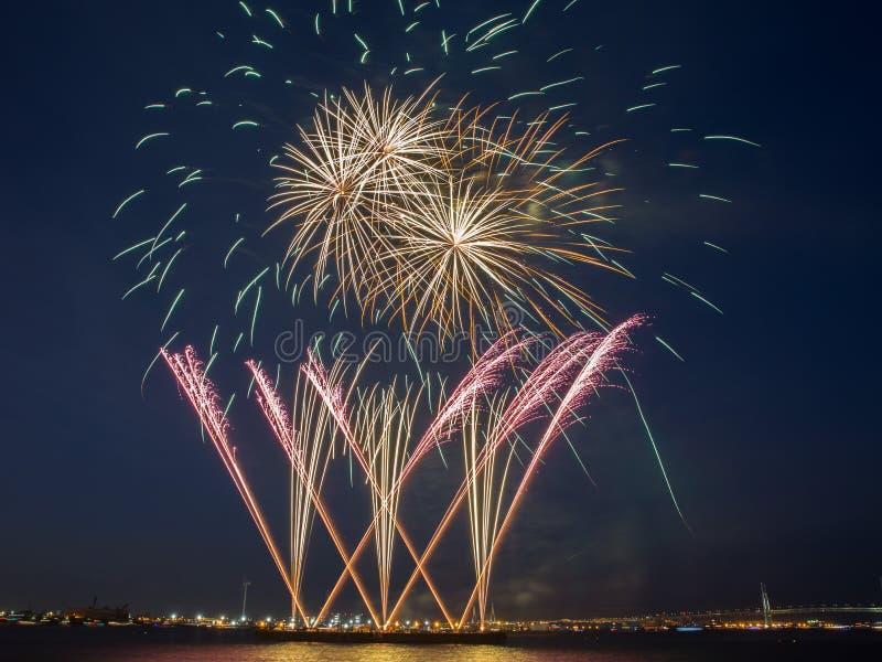 Åtskillig färgrik fyrverkeribristning i natthimlen med ljusslingor och guld- cirklar av fyrverkerier royaltyfri fotografi
