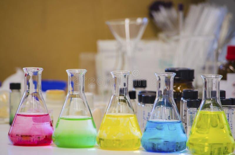 Åtskillig färgrik lösning i den koniska flaskan som fodras på en bänk i en kemilabb med experiment för organisk kemi för suddighe royaltyfri fotografi