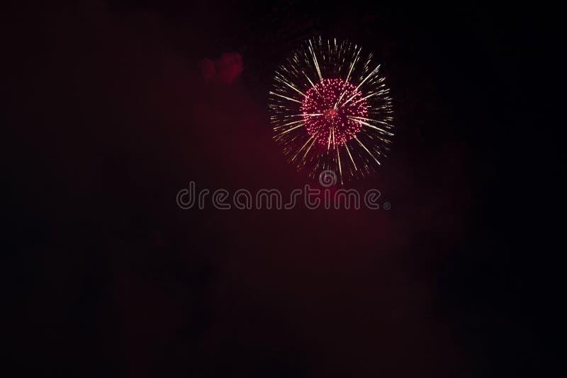 Åtskillig fyrverkerier i natthimmel i en sammansättning i skuggaguld och rött arkivfoto