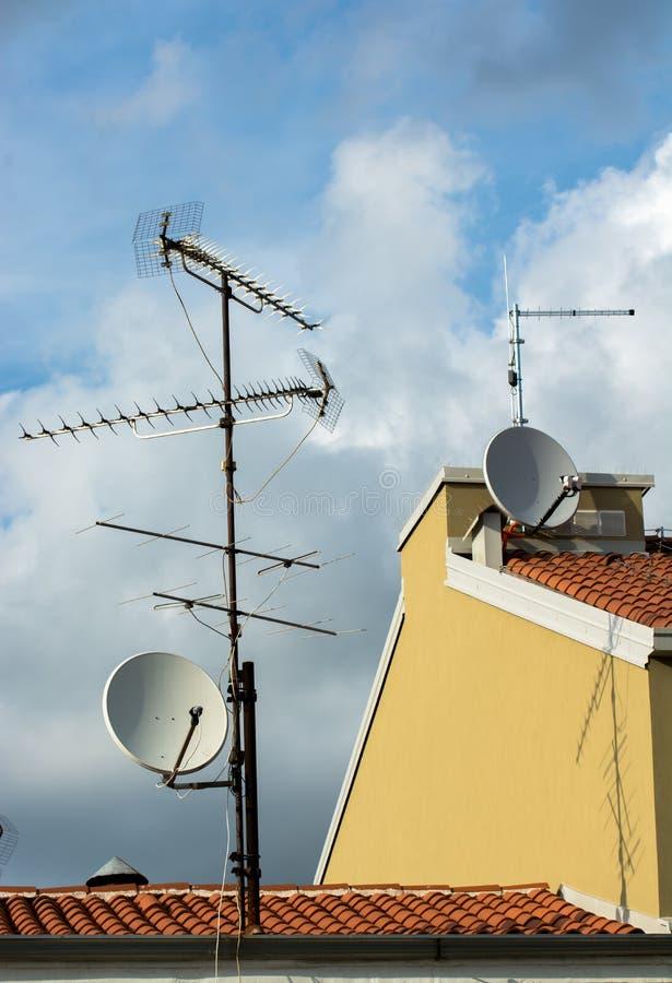 Åtskilliga antenner på tak arkivfoton