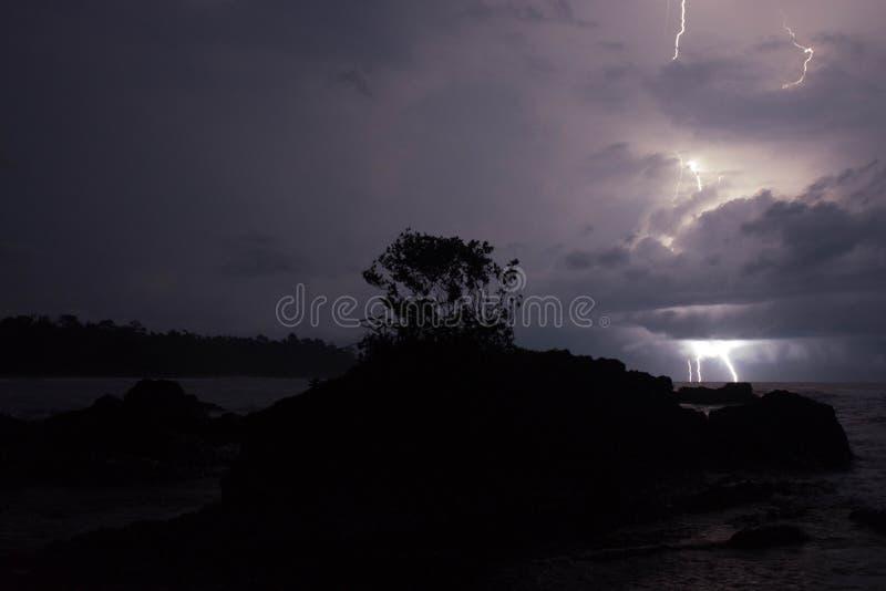 Åtskilliga blixtslag över havet med ön royaltyfria bilder