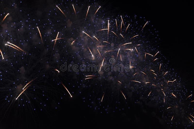Åtskilliga fyrverkerier i natthimmel i en sammansättning i blåa skuggor som är guld- och arkivbild