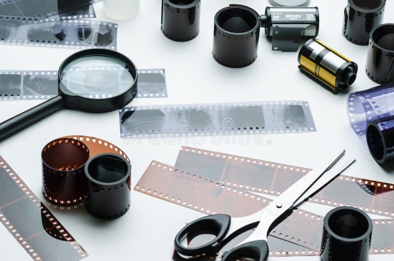 Åtskilliga 35mm fotografisk film och förstoringsglas på vit bakgrund arkivfoton