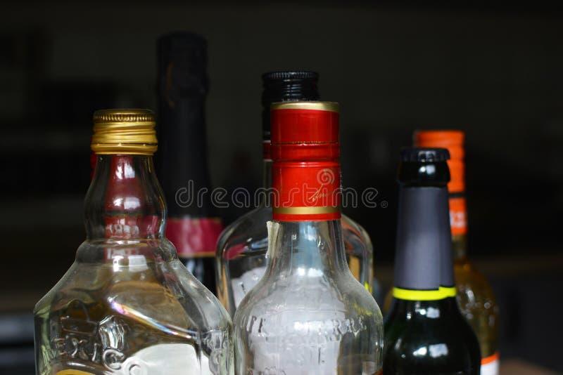 Åtskilliga olika starka andealkoholflaskor på svart bakgrund royaltyfri foto