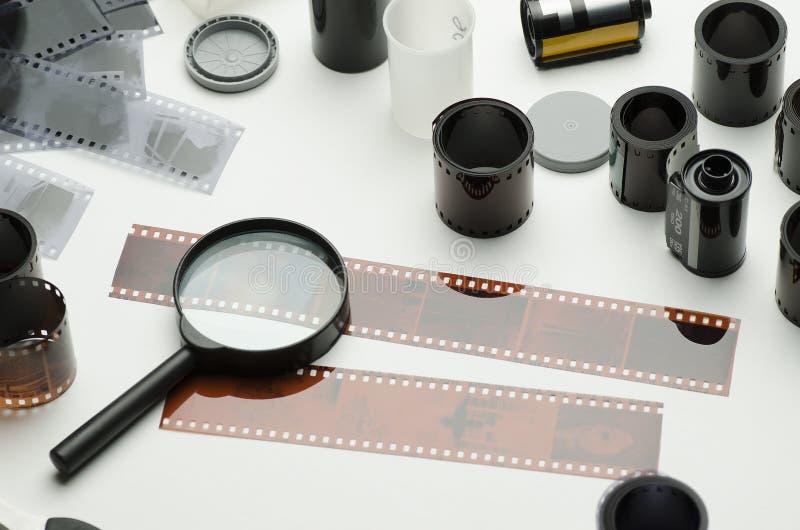 Åtskilligt fotografiska filmer, sax och förstoringsglas på vit bakgrund royaltyfria foton