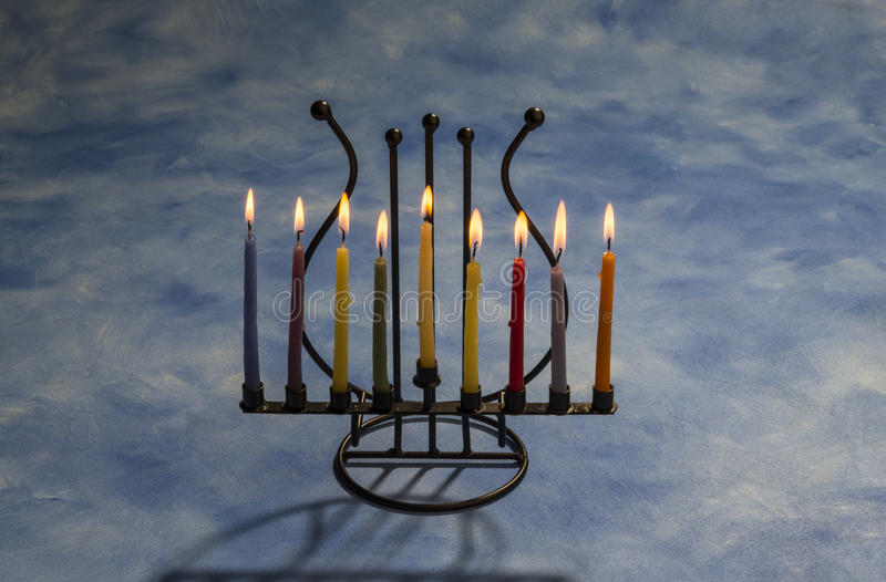 Åtta brinnande Chanukkahstearinljus i menoror fotografering för bildbyråer