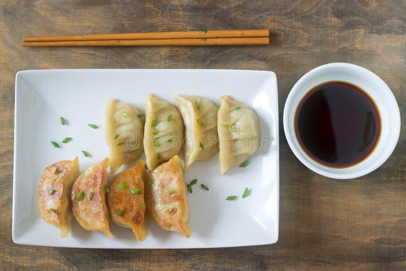 Åtta kokade eller stekte jiaozi, eller gedzaen tjänade som med soya royaltyfri foto