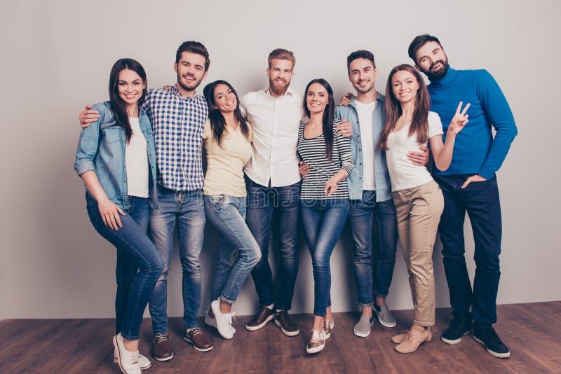 Åtta lyckliga vänner poserar nära väggen, le och gesturen arkivbilder