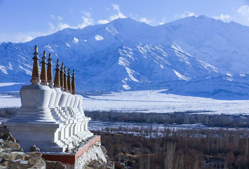 Åtta tibetana stupas med himalaya bergskedja i bakgrund royaltyfria bilder
