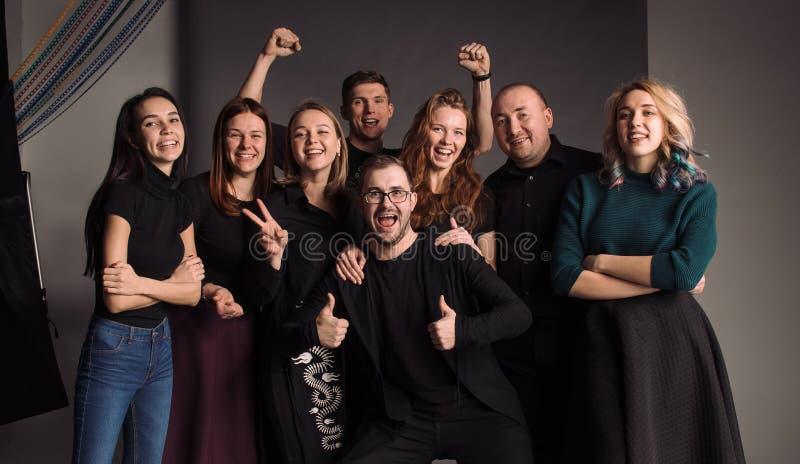 Åtta unga vänner som tillsammans står, kramar, skrattar och ler Studioskottet i den gråa väggen arkivbild