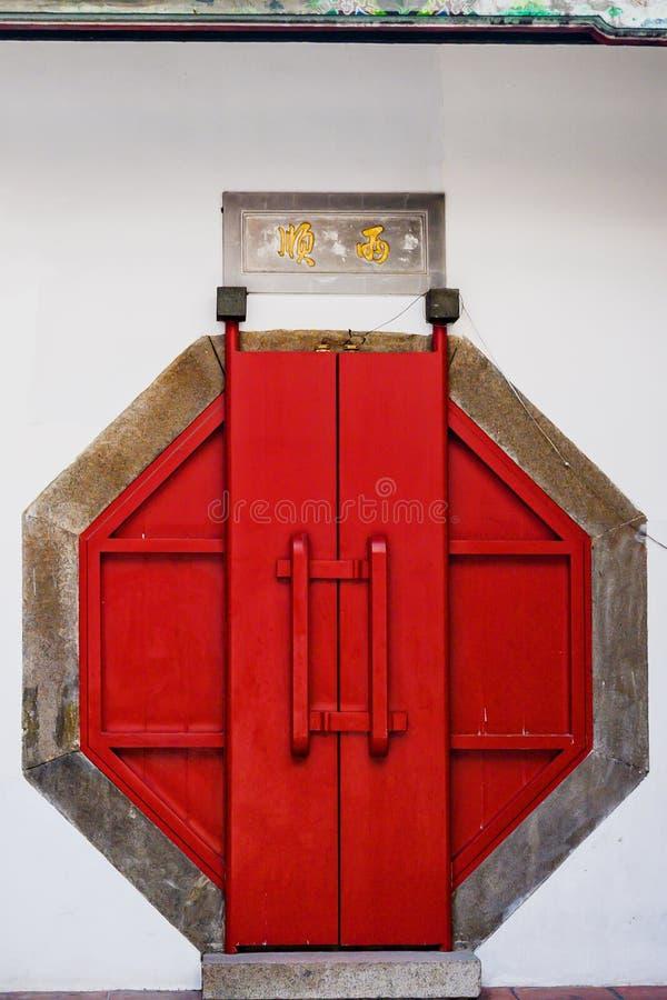 Åttahörnig röd dörr, ingång till den buddistiska taiwanesiska templet, Tainan, Taiwan royaltyfri bild