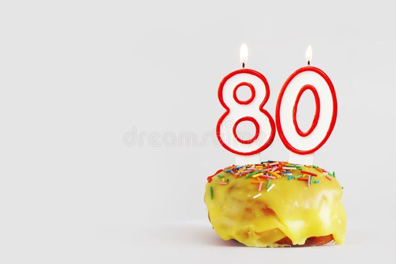 Åttio år årsdag Födelsedagmuffin med vita brinnande stearinljus med den röda gränsen i form av nummer 80 arkivfoto