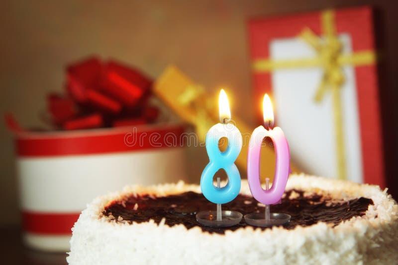 Åttio år födelsedag Kaka med bränningstearinljus och gåvor royaltyfria foton