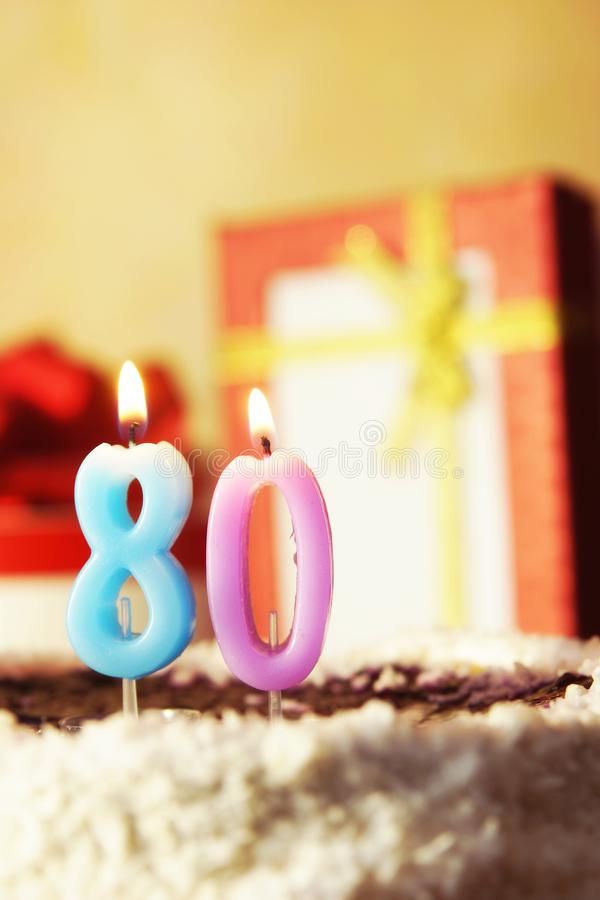 Åttio år stearinljus för födelsedagburningcake royaltyfri bild