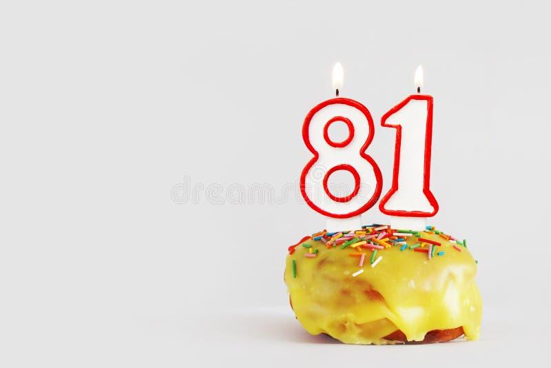 Åttio en år årsdag Födelsedagmuffin med vita brinnande stearinljus med den röda gränsen i form av nummer 81 royaltyfri fotografi