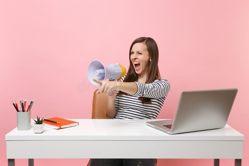 恼怒的妇女尖叫在指向食指的扩音机工作在有被隔绝的个人计算机膝上型计算机的白色书桌坐柔和的淡色彩 库存图片