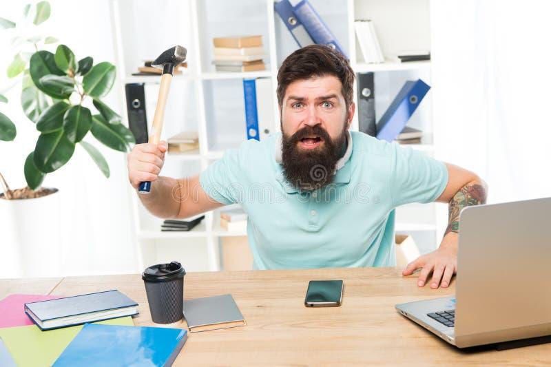 恼怒的积极的商人在办公室 沮丧的办公室工作者藏品锤子保持了平衡准备好捣毁 办公室生活做 库存照片