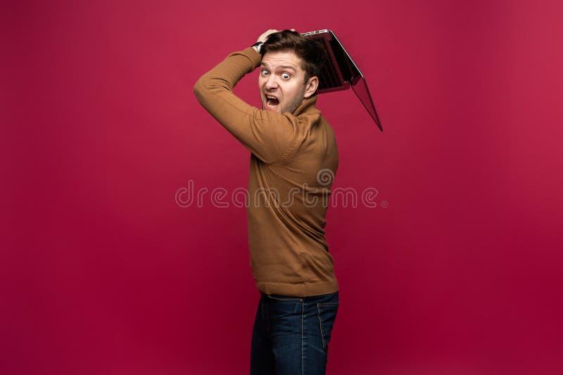 恼怒的生气被激怒的人画象偶然叫喊和举行的银色膝上型计算机的被隔绝在桃红色背景 库存照片