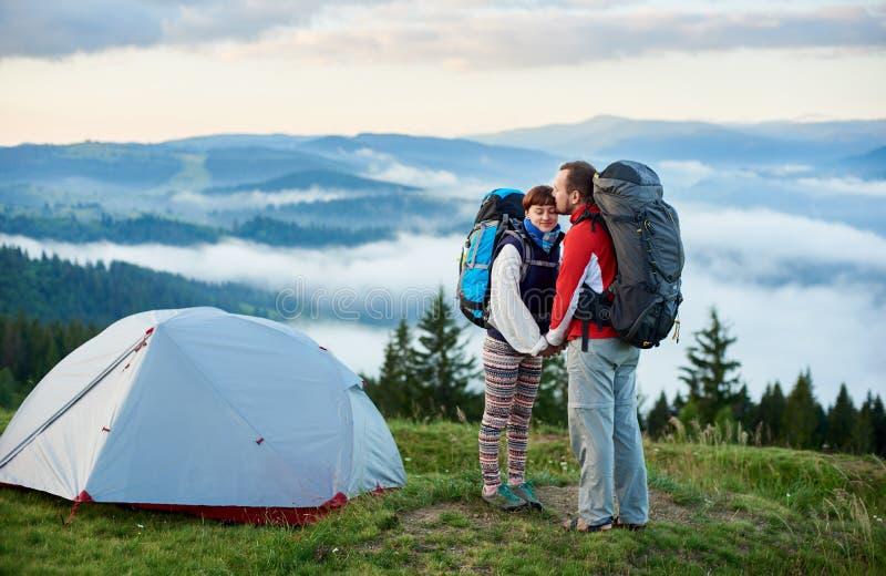 恋人活跃休息浪漫夫妇在山的在野营附近的早晨 库存图片