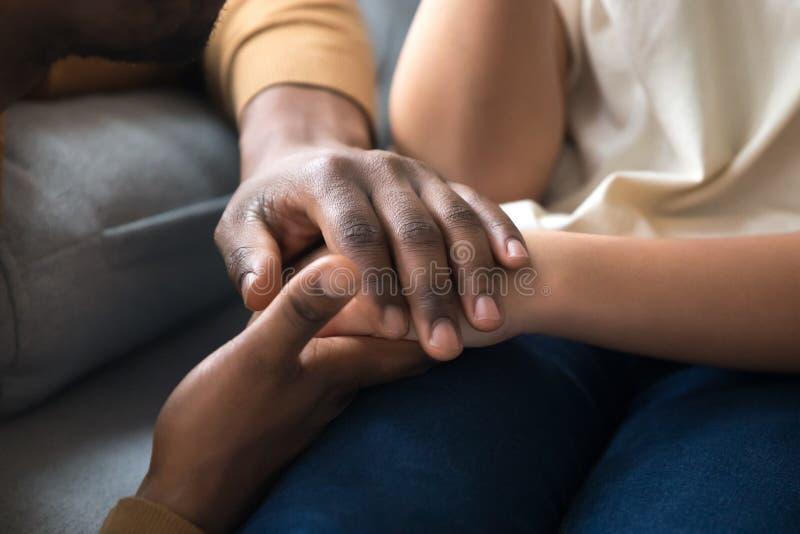 握孩子的手的非洲父亲作为慈善支持概念 免版税库存图片