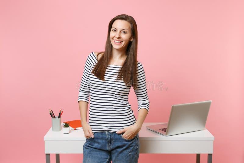 握在口袋工作的手和站立在有在粉红彩笔隔绝的个人计算机膝上型计算机的白色书桌附近的年轻成功的妇女 库存图片