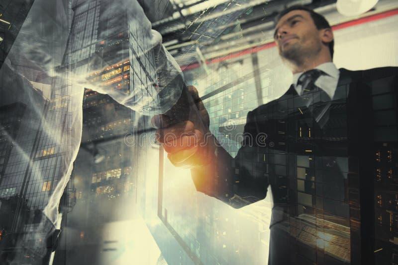 握手企业人在有网络作用的办公室 配合和合作的概念 两次曝光 免版税库存照片