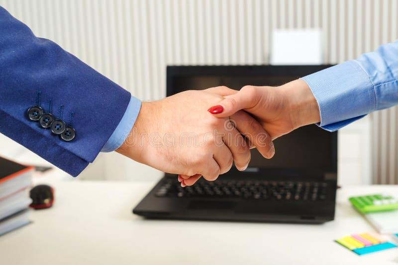 握手的买卖人在办公室 男人和妇女结束的生意 企业生意人cmputer服务台膝上型计算机会议微笑的联系与使用妇女 商务伙伴,公司 免版税库存图片