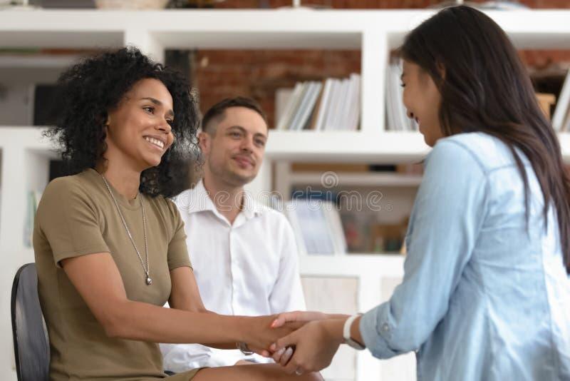握手的亚裔和非洲妇女在小组疗期期间 免版税库存照片