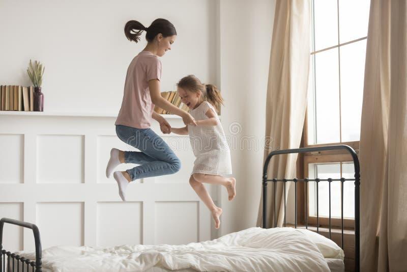 握手的愉快的妈妈和孩子女孩跳跃在床上 免版税库存图片