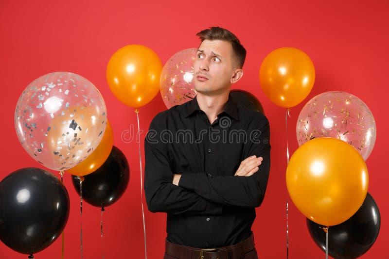握手的黑经典衬衣的好奇生气年轻人折叠了,看在旁边在红色背景气球 ST 库存照片