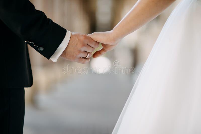 握新娘的手的新郎,当走时 免版税库存图片