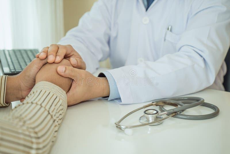 握耐心手的友好的人医生手坐在鼓励、同情,欢呼和医疗支持的一会儿的书桌 库存照片