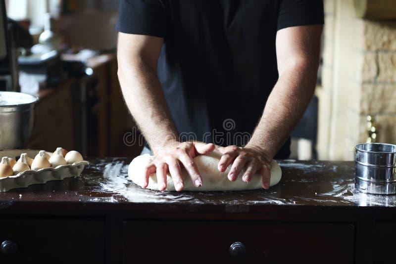 揉在厨房用桌上的男性手新鲜的面团 免版税库存图片