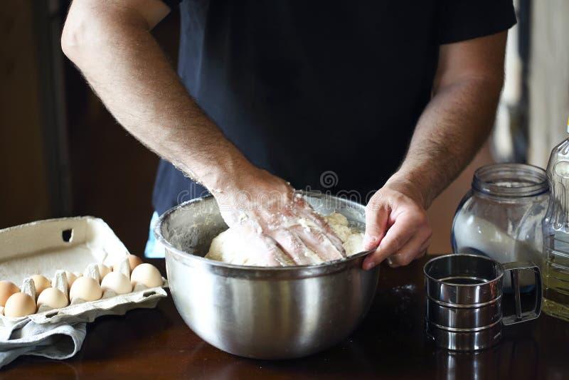 揉在厨房用桌上的男性手新鲜的面团 免版税库存照片