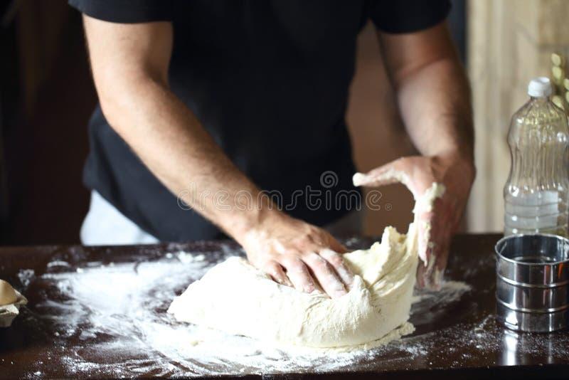 揉在厨房用桌上的男性手新鲜的面团 免版税图库摄影