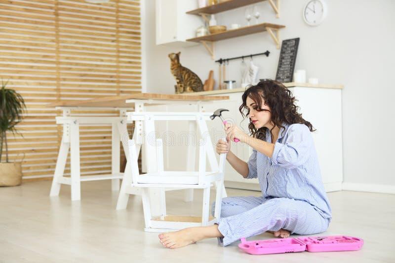 搬入有螺丝刀的新的公寓聚集的家具的妇女 搬入新公寓聚集的妇女 图库摄影
