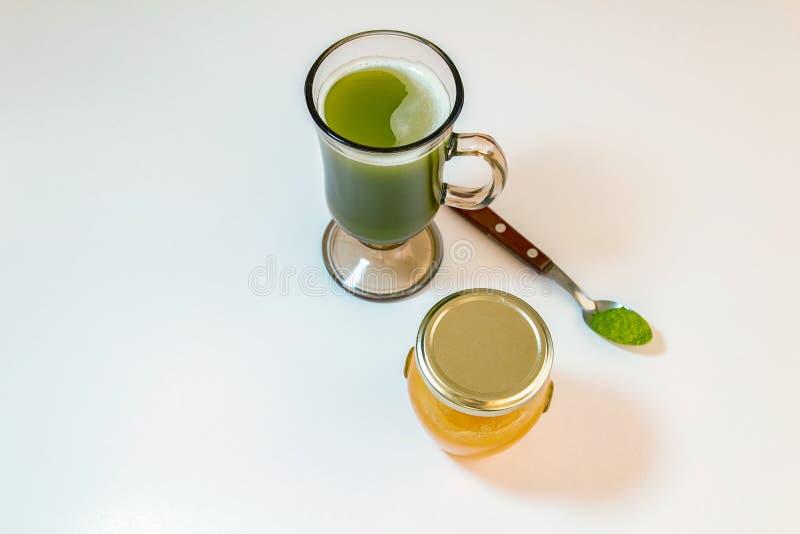 杯与绿茶粉末的macha绿茶在匙子和小瓶在白色背景的蜂蜜 库存照片