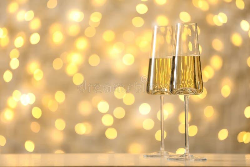 杯反对被弄脏的彩色小灯的泡沫腾涌的香槟 免版税图库摄影