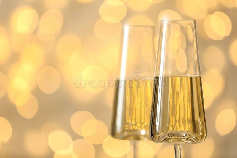 杯反对被弄脏的彩色小灯的泡沫腾涌的香槟 库存照片