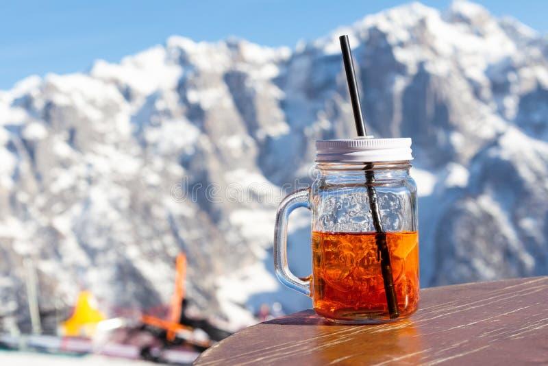 杯子aperol在街道咖啡馆的桌上站立在滑雪场的倾斜的 库存图片