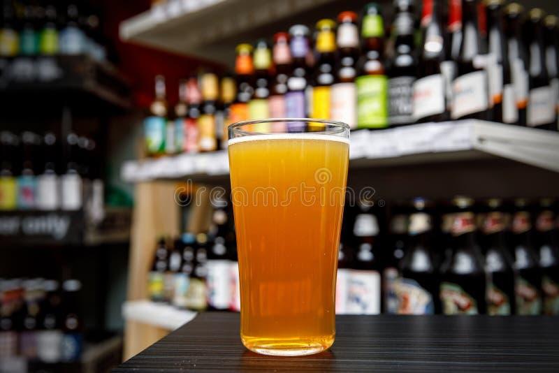 杯在酒吧的工艺啤酒 瓶的分类在被弄脏的背景的 免版税库存照片