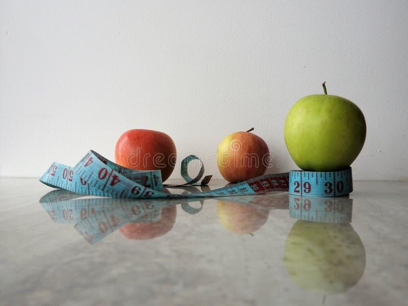 杯苹果酸奶饮料、绿色苹果、笔记本、铅笔和测量的磁带 图库摄影