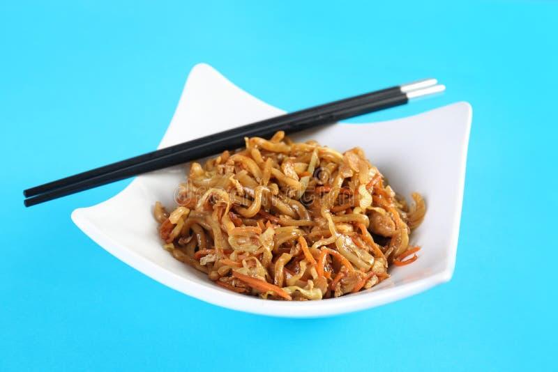 板材用中国面条和筷子在颜色背景 免版税图库摄影
